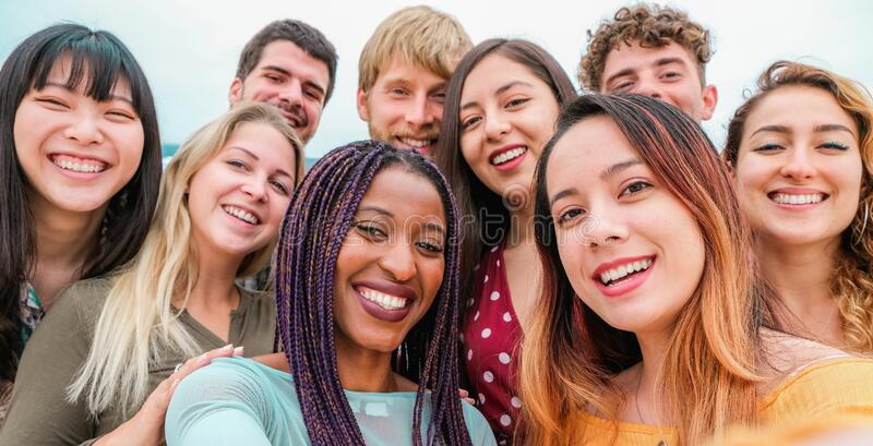 Young friends from diverse cultures and races taking photo making happy faces - Youth, millennial generation and friendship. Concept with students people having royalty free stock images