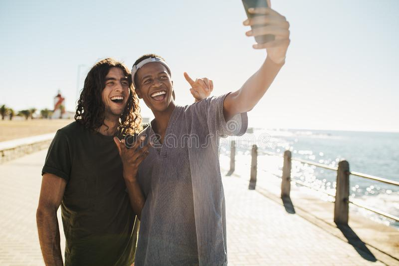 Friends make a selfie on the seaside hangout. Young friends doing selfie standing on a road by the beach. Friends make a selfie on the seaside hangout stock photo