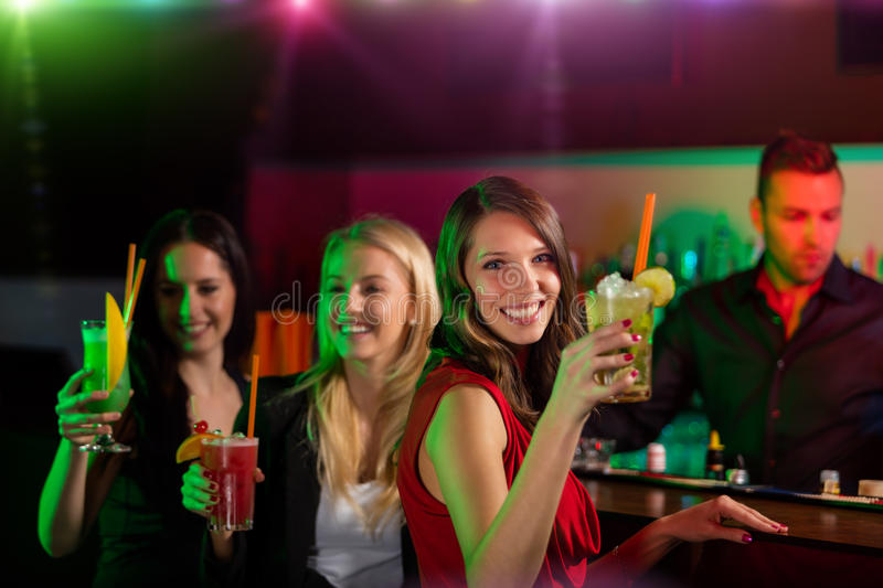Young friends drinking cocktails together at party stock photo