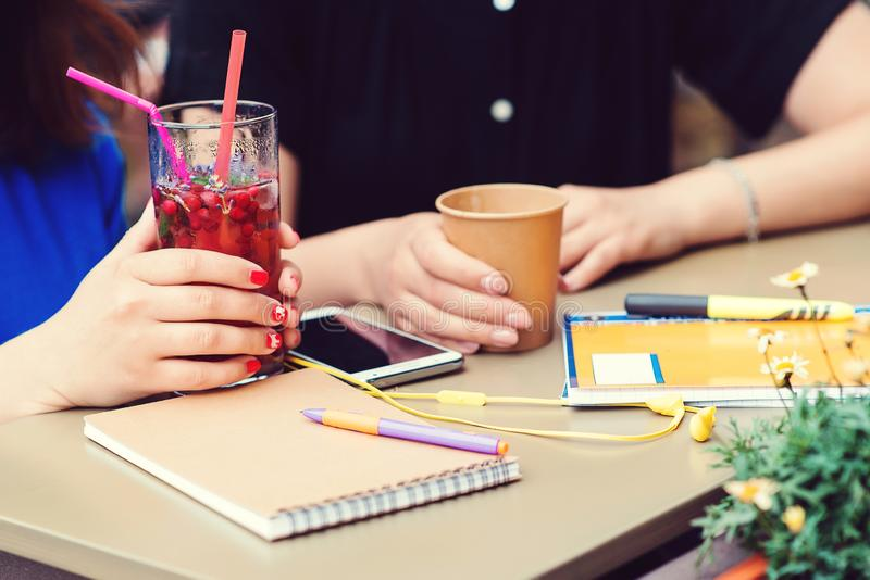 Young friends drinking coffee and lemonade in bar restaurant. People hands doing break outdoors cafeteria. Job break, notebook and royalty free stock photo