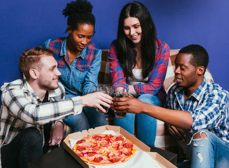 Young friends eat pizza with soda at home, cheers. Young friends international company eat pizza with soda, cheers. Four happy people together, fun leisure, home stock photography