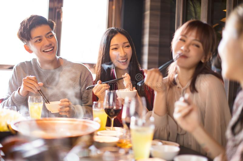 Young friends enjoy dinner in hot pot restaurant royalty free stock photography