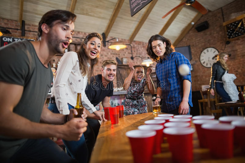 Young friends enjoying beer pong game in restaurant stock images