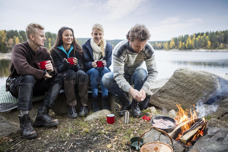 Young Friends Enjoying Camping On Lakeshore royalty free stock image