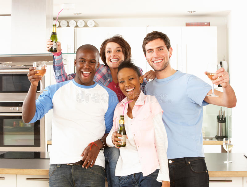Young Friends Enjoying Drink In Kitchen stock photography