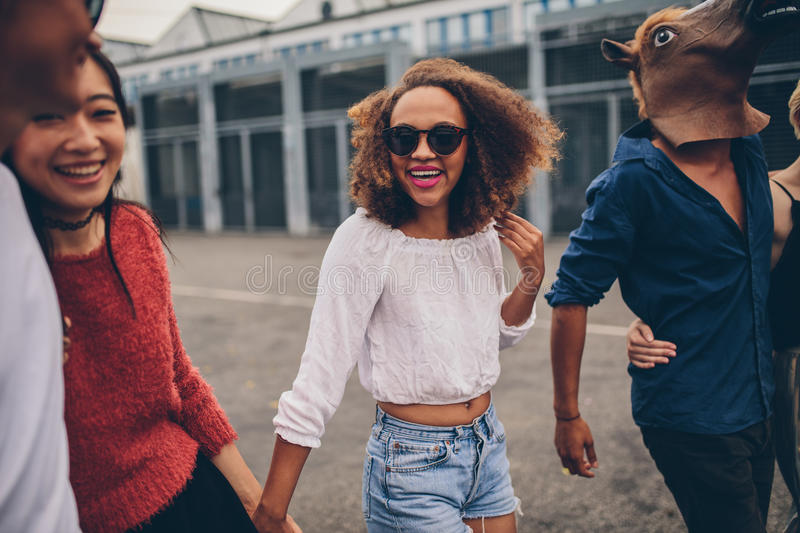 Young friends enjoying together outdoor. Shot of young friends enjoying together outdoors. Multiracial group of young people walking on the street and having fun royalty free stock photography
