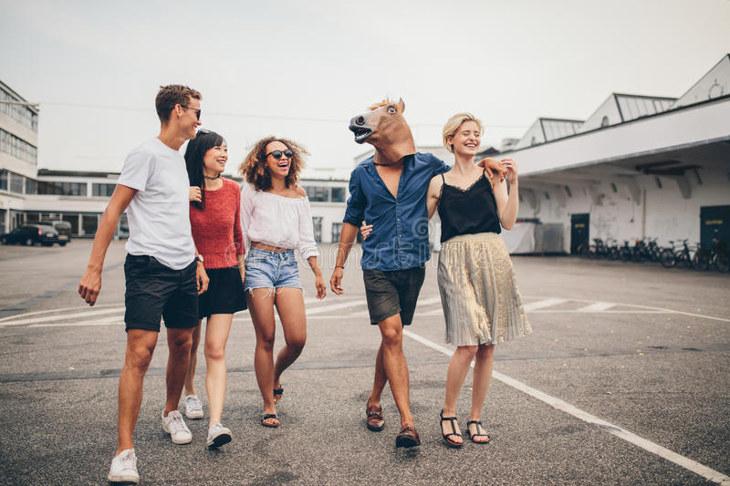 Young friends enjoying together on the street. Full length shot of young friends enjoying together on the street. Multiracial group of young people walking stock photography
