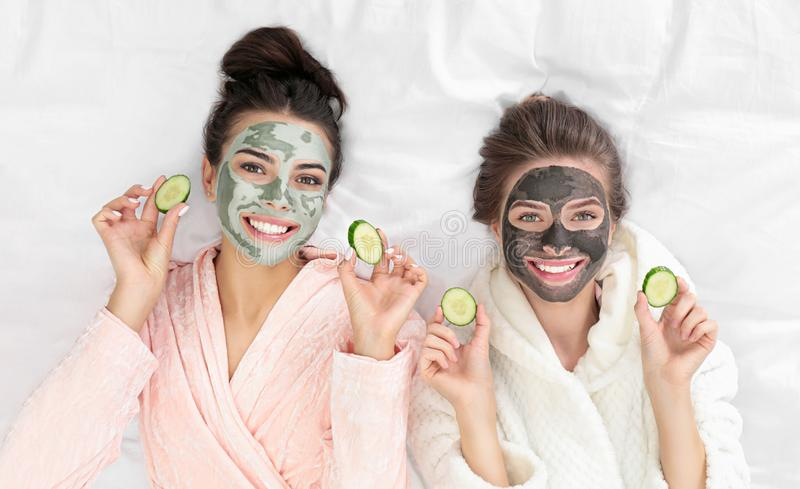 Young friends with facial  having fun on bed at pamper party, top view. Young friends with facial masks having fun on bed at pamper party, top view royalty free stock photos