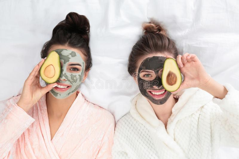 Young friends with facial masks  fun on bed at pamper party, top view. Young friends with facial masks having fun on bed at pamper party, top view stock images