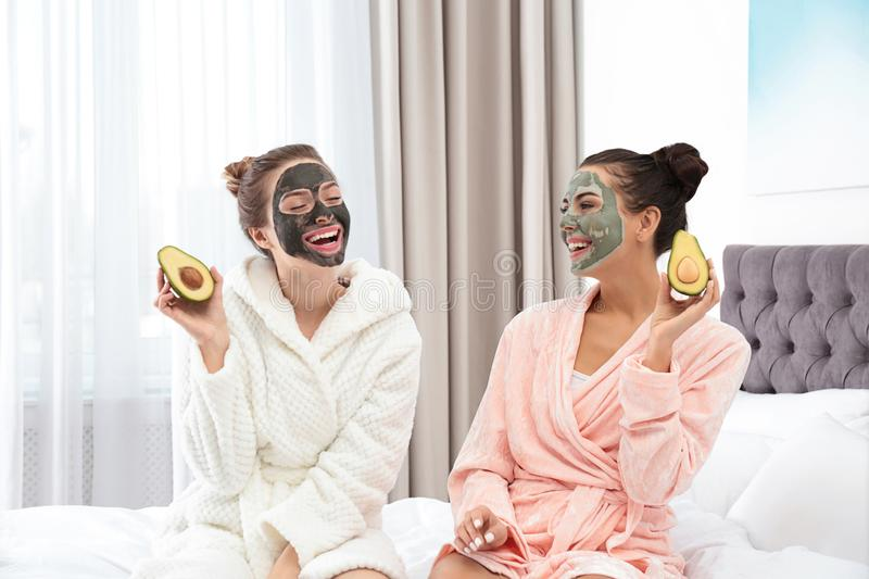 Young friends with facial masks having fun in bedroom royalty free stock images