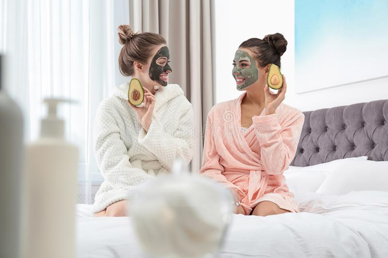 Young friends with facial masks having fun in bedroom at party royalty free stock photography