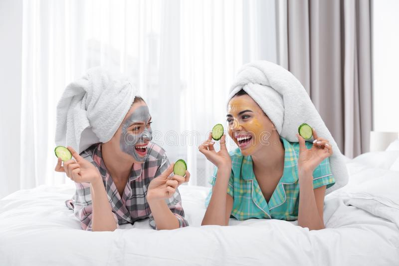 Young friends with facial masks having fun in bedroom stock image