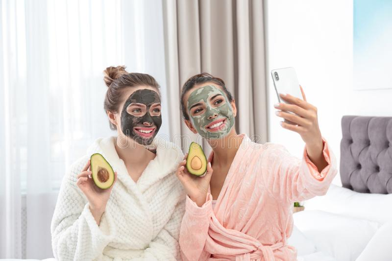 Young friends with facial masks taking selfie in bedroom stock image