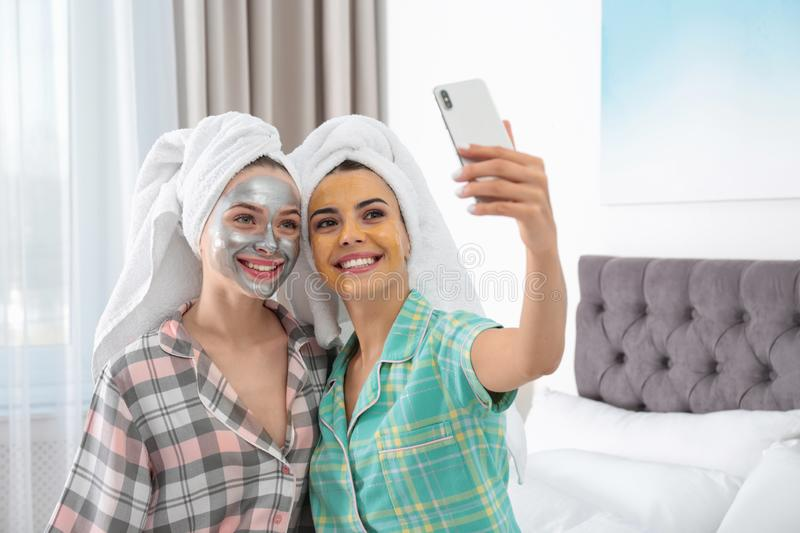 Friends with facial masks taking selfie in bedroom at pamper party royalty free stock photo