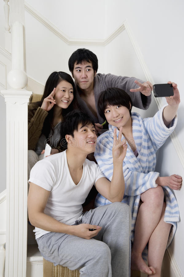 Young friends gesturing peace sign while taking self photograph stock images