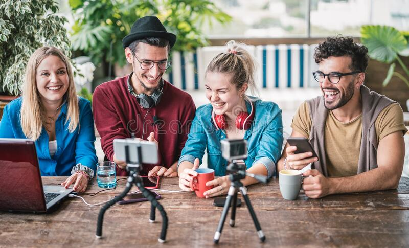 Young friends group sharing info on streaming platform with webcam - Startup marketing concept with millennial guys and girls royalty free stock photo
