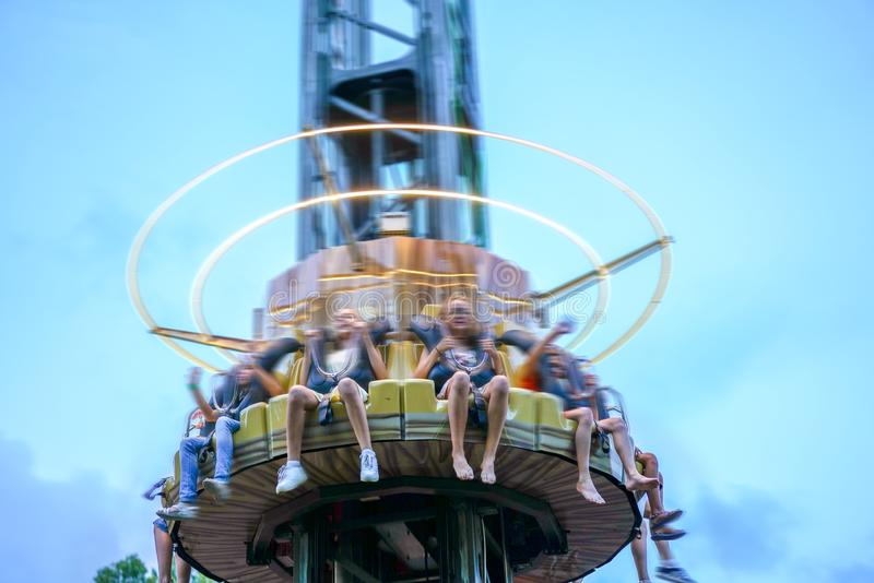 Young friends have fun in the park. Happy guys ride on attractions. Entertainment park, amusement, sky thrill. Young friends have fun in the park. Happy guys royalty free stock photo
