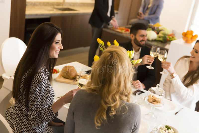 Young friends having dinner at home and toasting royalty free stock photography