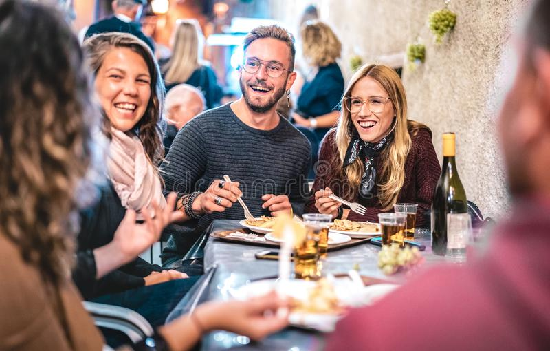 Young friends having fun drinking white wine at street food festival - Happy people eating local plates at open air restaurant stock photos