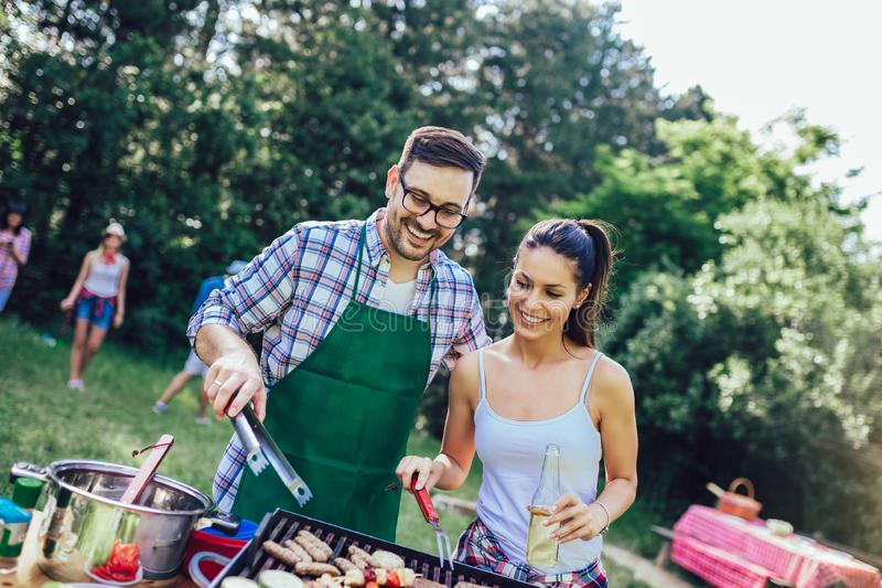 Friends having fun grilling meat enjoying barbecue party stock photography