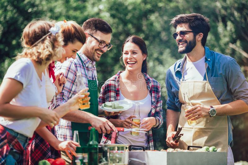 Friends having fun grilling meat enjoying barbecue party. Young friends having fun grilling meat enjoying barbecue party stock images