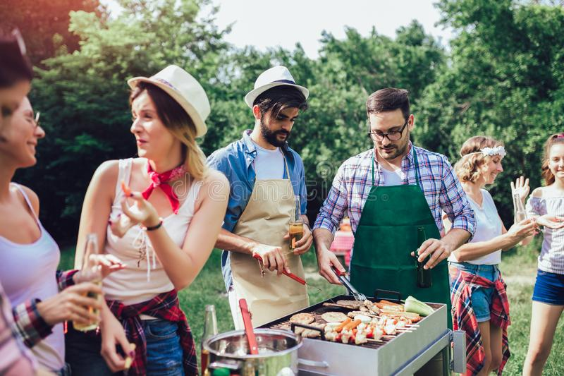 Friends having fun grilling meat enjoying barbecue party stock images