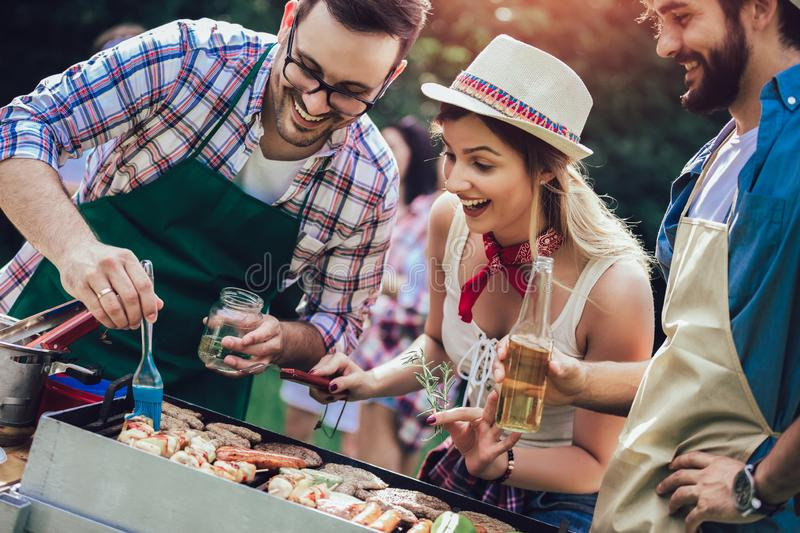 Friends having fun grilling meat enjoying barbecue party stock image