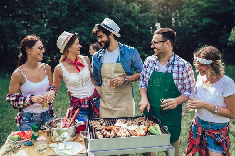 Friends having fun grilling meat enjoying barbecue party stock photo