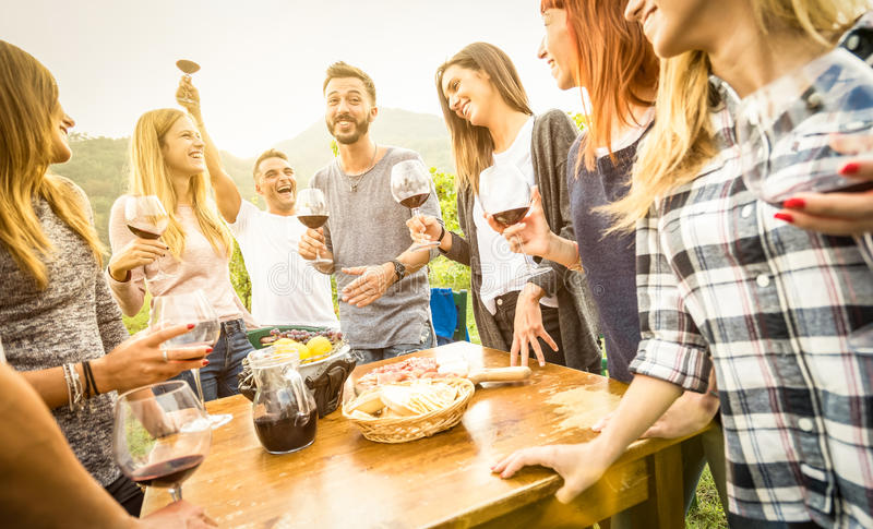 Young friends having fun outdoor drinking red wine - Happy peopl stock image
