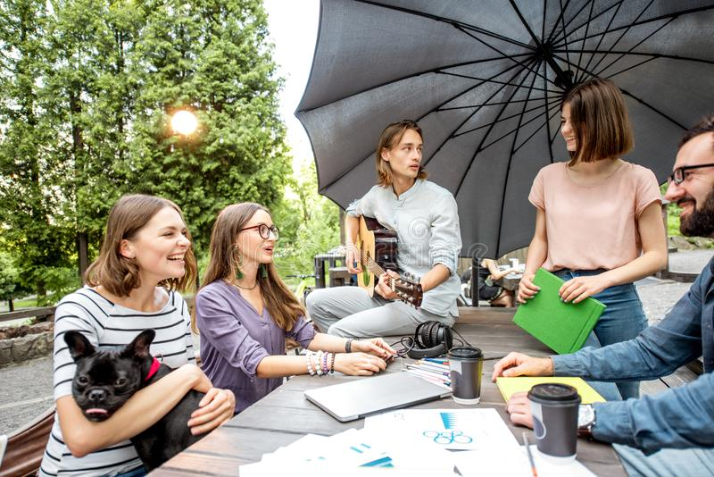 Friends having fun together during a study outdoors. Young friends having fun playing guitar and playing wiwth dog outdoors in the park stock images