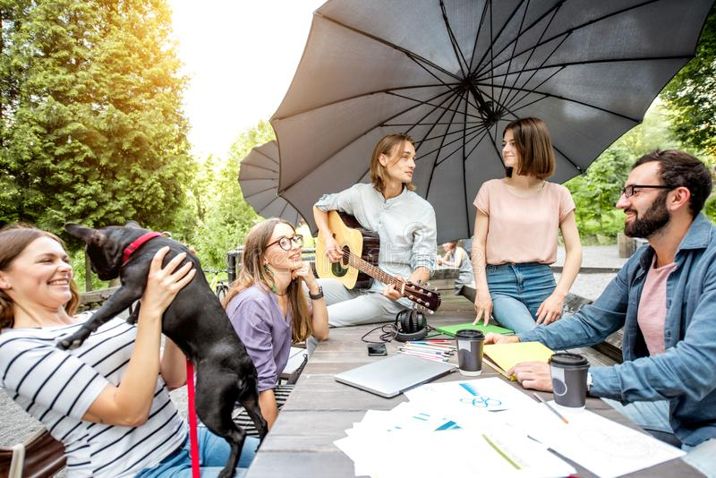 Friends having fun together during a study outdoors. Young friends having fun playing guitar and playing wiwth dog outdoors in the park royalty free stock photos