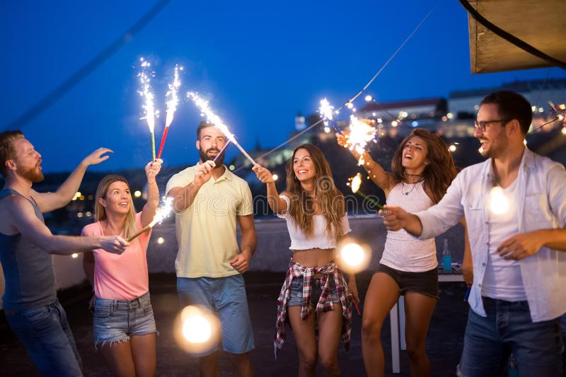 Young friends having fun at a rooftop party, playing the guitar, singing, dancing and drinking royalty free stock photo