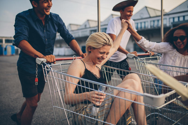 Young friends having fun on a shopping carts royalty free stock photo