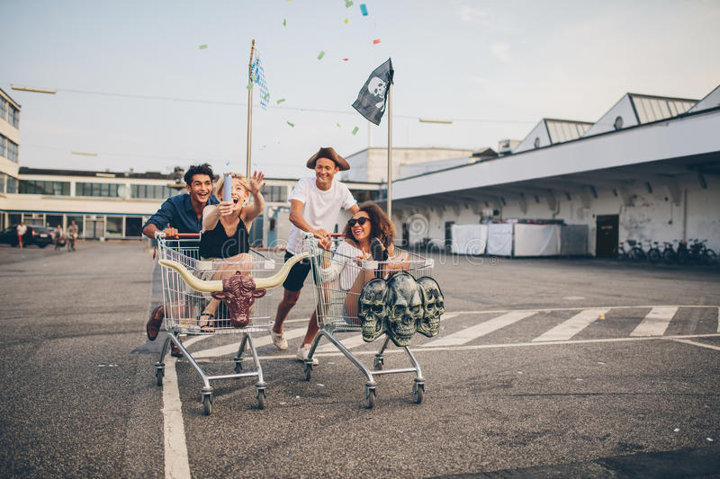 Young friends having fun on a shopping trolleys. Multiracial group of friends racing with shopping cart. Young people racing with shopping trolleys on road royalty free stock images