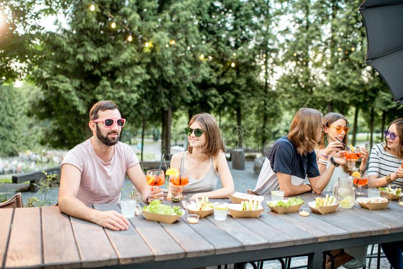 Friends with snacks and drinks in the park cafe. Young friends having fun together with snacks and drinks during the evening light outdoors in the park cafe royalty free stock photos