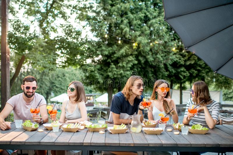 Friends with snacks and drinks in the park cafe. Young friends having fun together with snacks and drinks during the evening light outdoors in the park cafe royalty free stock images