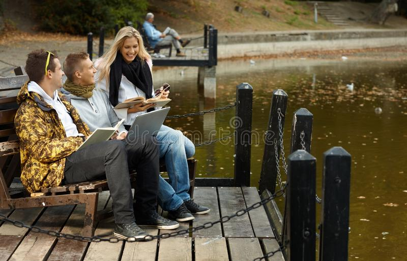 Young friends by lake smiling stock photos