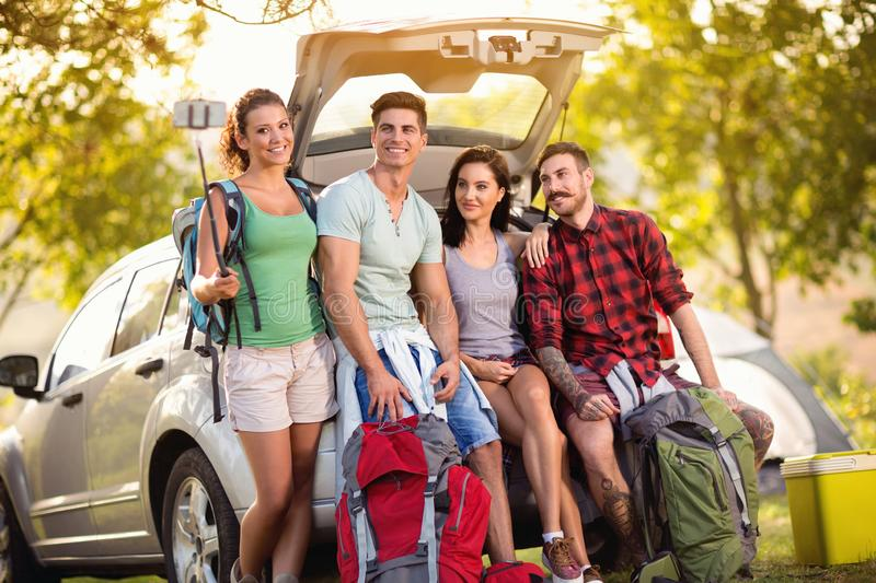 Young friends make selfie photo with smartphone in the trunk on camping trip stock photos
