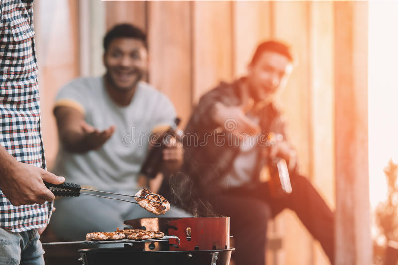 Young friends making barbecue on porch with back light. Happy young friends making barbecue on porch with back light stock photo