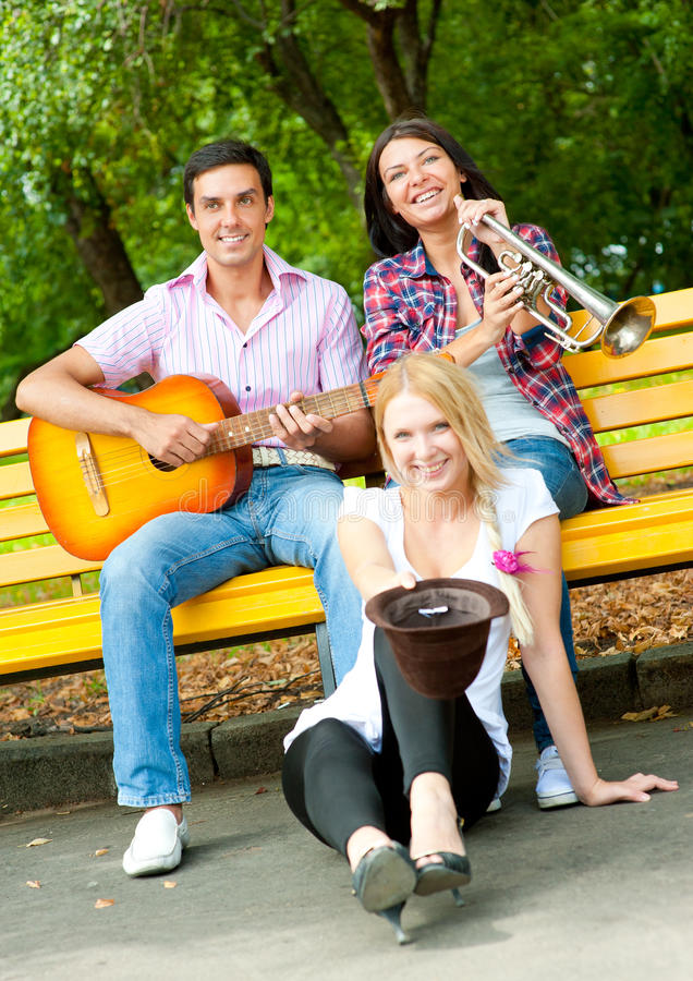 Young Friends Play The Guitar And Trumpet Royalty Free Stock Image