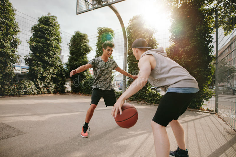 Young friends playing basketball together royalty free stock photography