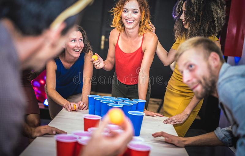 Young friends playing beer pong at youth hostel - Free time travel concept with backpackers having unplugged fun at guesthouse royalty free stock image