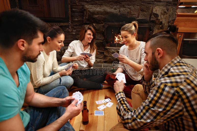 Young friends playing cards together. On winter holiday on mountain royalty free stock images