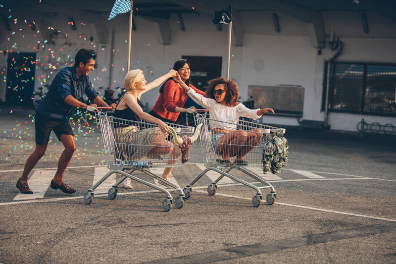 Young friends racing with shopping carts. Young friends having fun on shopping carts. Multiracial young people racing on shopping cart stock photo