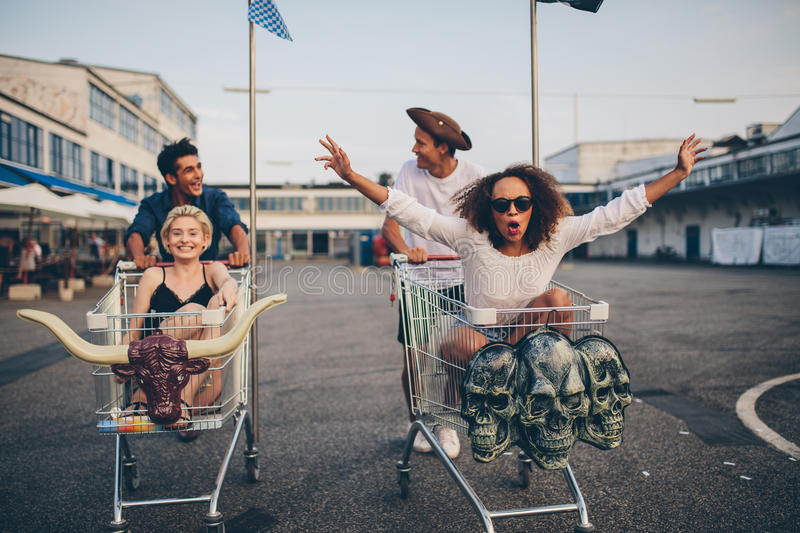 Young friends racing with shopping carts stock photography