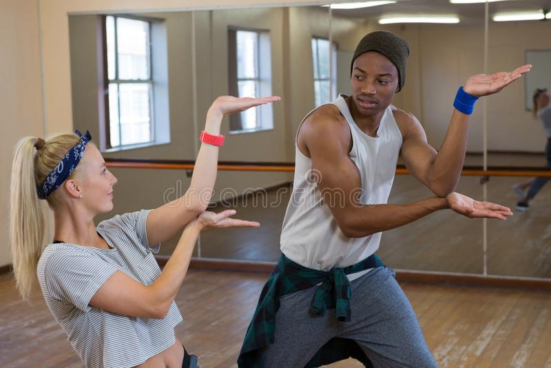 Friends rehearsing dance against mirror on wooden floor. Young friends rehearsing dance against mirror on wooden floor at studio stock photos