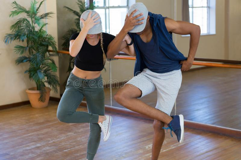 Young friends rehearsing dance. By mirror in studio stock photos