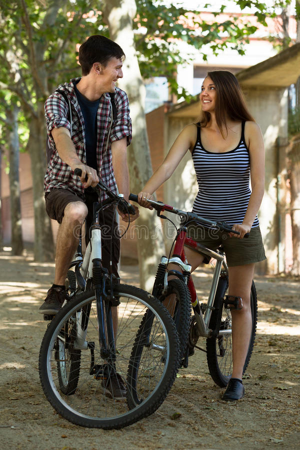 Young friends relaxing in the park. Young smiling friends relaxing in the park with bicycles stock image