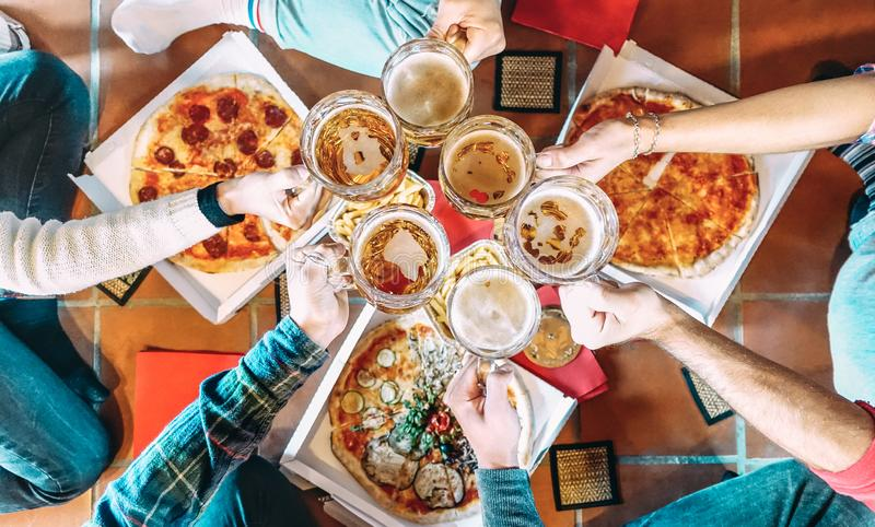 Young friends roomates eating take away pizza at home after college - Friendship concept with people students enjoying time royalty free stock photography