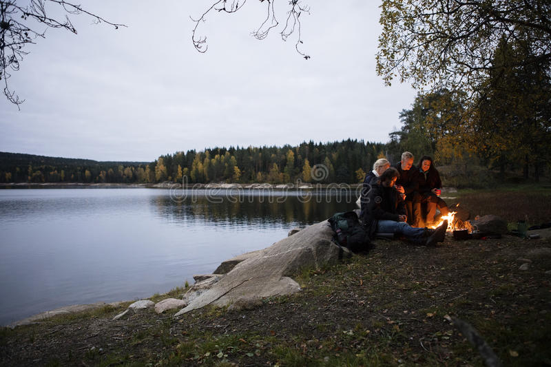 Young Friends Sitting Near Bonfire By Lake At Dusk royalty free stock image